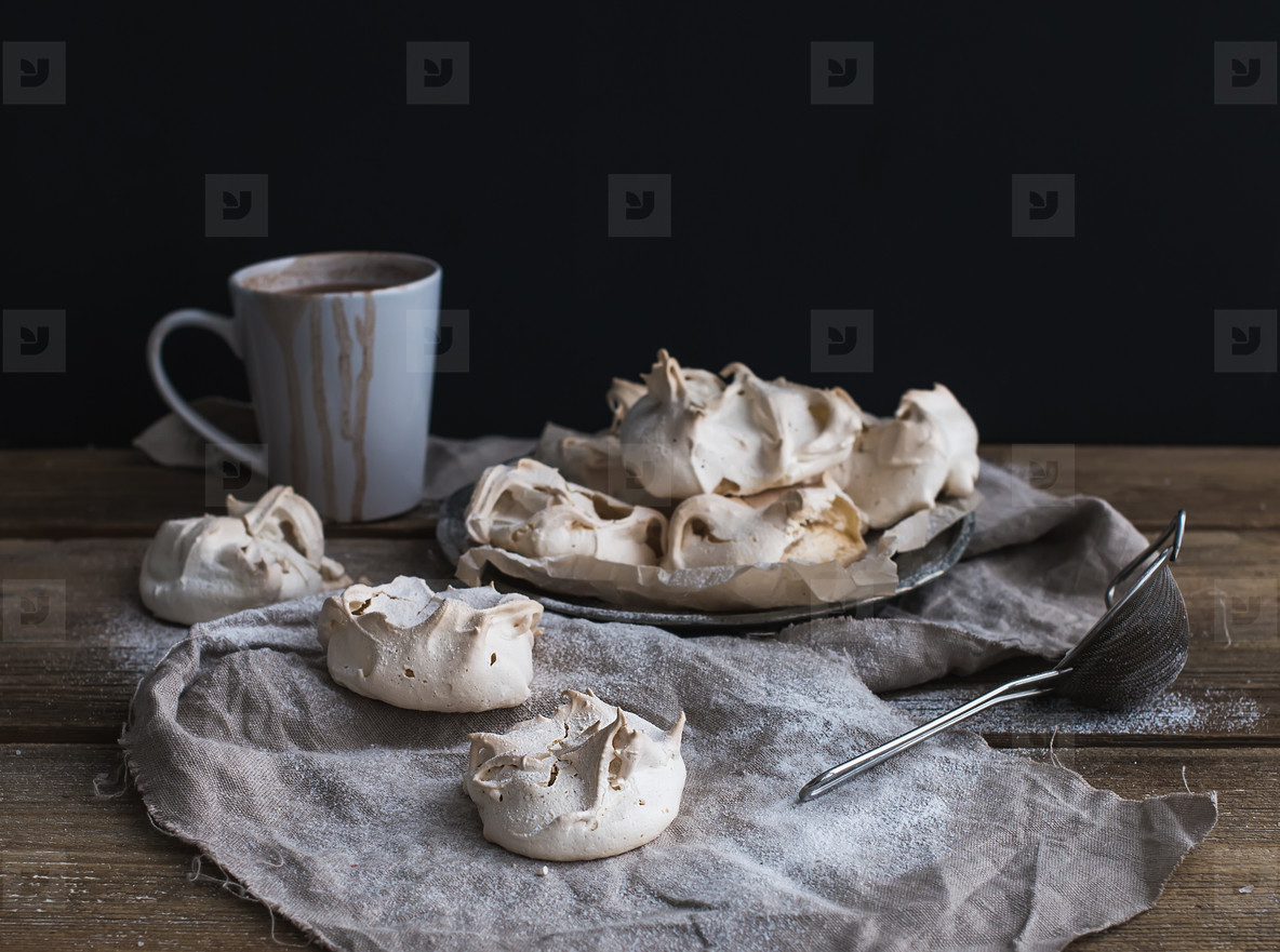 White meringue and mug of hot chocolate on a rustic wooden table  Black backdro