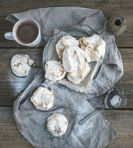 White meringue and mug of hot chocolate on a rustic wooden table Black background top view