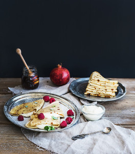 Thin pancakes or crepes with fresh raspberry  cream  mint  on a rustic wooden desk
