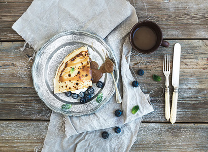 Thin pancake or crepe with fresh blueberry  cream  mint  and salty caramel sauce in vintage metal plate over rustic wooden backdrop