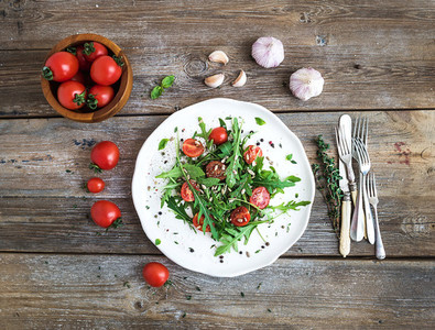 Salad with arugula  cherry tomatoes  sunflower seeds and herbs on white ceramic plate over rustic wood background