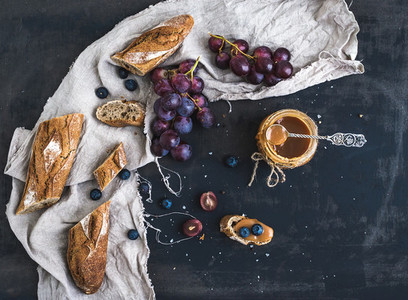 French baguette cut into pieces  red grapes  blueberry and salt caramel sauce on rustic dark background