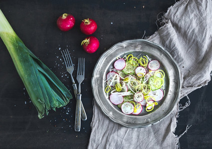 Spring salad with leek radish and cucumber in vintage metal plate