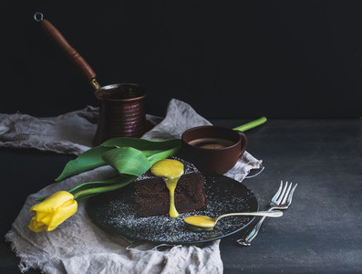 Perfect morning set for woman  Piece of truffle chocolate cake with lemon curd icing  hot coffee and yellow tulip on dark backdrop