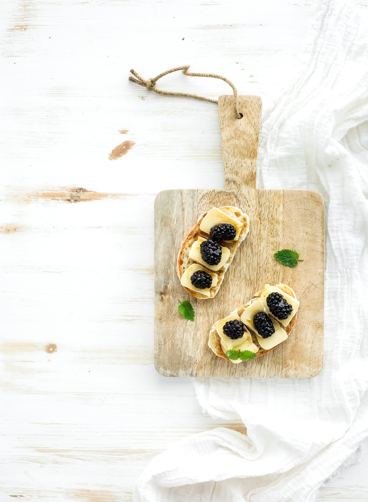 Bruschetta sandwich with brie cheese  honey and blackberry on rustic serving board over white wooden background  top view