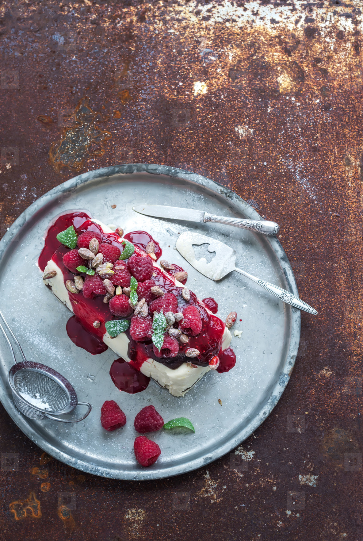 Semifreddo or italian cheese ice cream dessert with pistachios  fresh raspberries and mint on vintage silver tray over rusty grunge metal background  top view