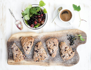 Fresh black currant scones with coffee and bowl of berries over rustic walnut wood serving board  top view