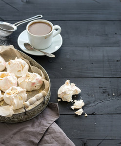 Almond meringues with cup of coffee on black rustic wooden table top view