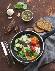 Pan of fried eggs  salami  asparagus  cherry tomatoes with bread  fresh basil  olives and garlic on grunge rusty table surface