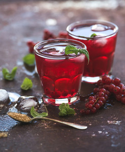 Red berry lemonade with ice and mint on grunge vintage rusty metal backdround