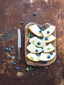 Melon and blueberries in a rustic wooden serving dish over grunge metal rusty background  top view