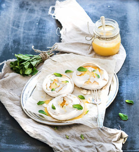 Merengues with lemon curd  fresh mint on silver tray  beige kitchen towel and grunge dark backdrop