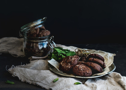 Dark chocolate chip cookies with fresh mint on dark backdrop