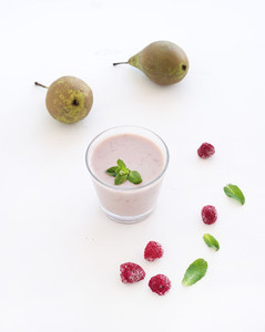 Glass of raspberry and pear smoothie with fresh mint leaves on white