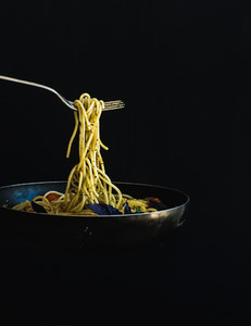 Hot spaghetti with tomatoes in cooking pan and fork on black backdrop