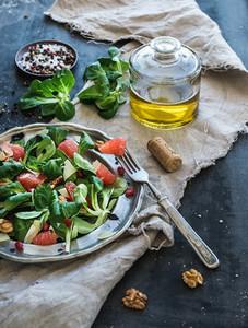 Spring salad with lamb s lettuce  grapefruit  garnet  walnuts and olive oil in vintage metal plate