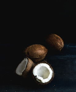 Whole and broken coconuts over dark grunge background