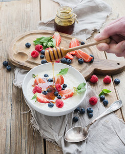 Healthy breakfast set  Rice cereal or porridge with berries and honey over rustic wood backdrop