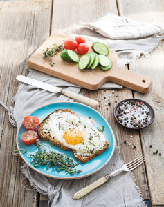 Breakfast set  Whole grain andwich with fried egg  vegetables and herbs on rustic wooden table  morning mood