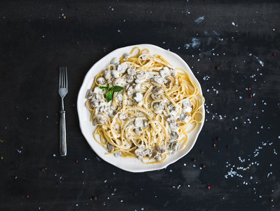 Pasta spaghetti with creamy mushroom sauce and basil in white ceramic plate over old grunge dark table