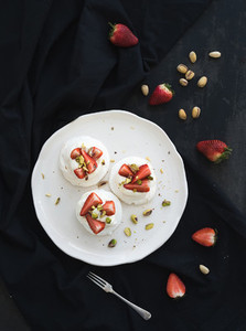 Small strawberry and pistachio pavlova meringue cakes with mascarpone cream  fresh mint over black backdrop