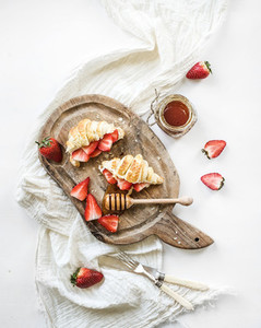 Freshly baked croissants with strawberries  mascarpone and honey on rustic wooden board over white backdrop