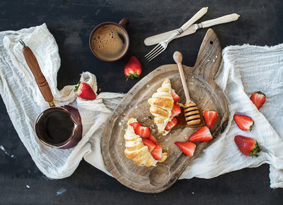 Breakfast set  Freshly baked croissants with strawberries  mascarpone  honey and coffee on rustic wooden board over dark grunge backdrop