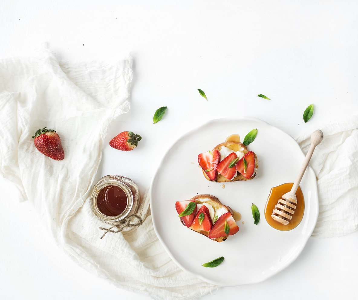 French toasts with strawberry  cream cheese  honey and mint on light ceramic plate