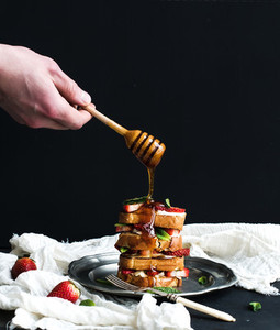 French toasts tower with strawberry  cream cheese and mint  hand is pouring honey over top of it