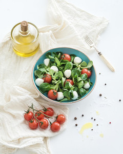 Spring salad with lambs lettuce mozarella and cherry tomatoes in blue ceramic bowl over white backdrop