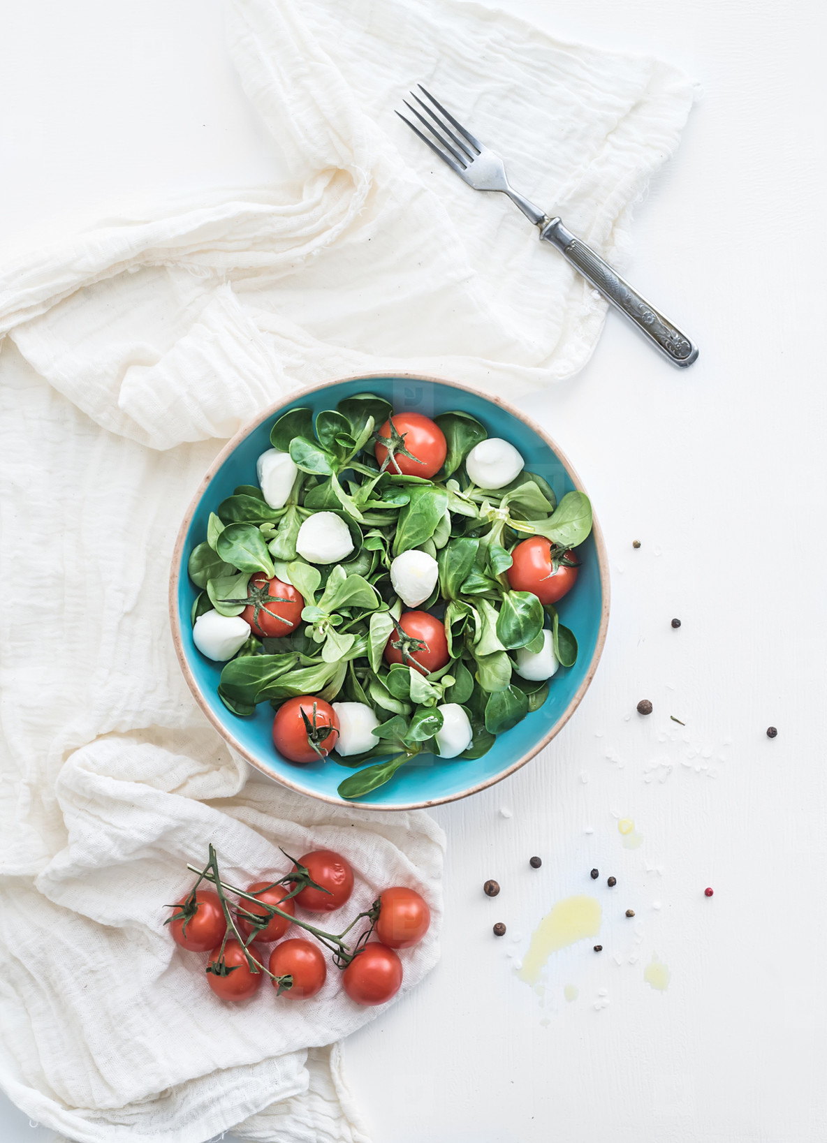 Photos - Spring salad with lamb's lettuce, mozarella and cherry-tomatoes in blue ceramic bowl over white backdrop
