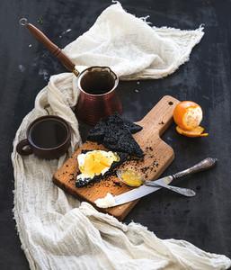 Breakfast set  Black bread toasts with tangerine marmelade and mascarpone cheese  fresh coffee on dark grunge backdrop