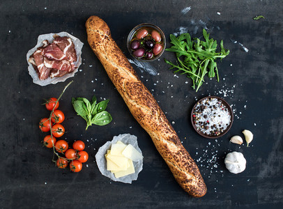 Ingredients for sandwich with smoked meat  baguette  basil  arugula  olives  cherry tomatoes  parmesan cheese  garlic and spices over black grunge background