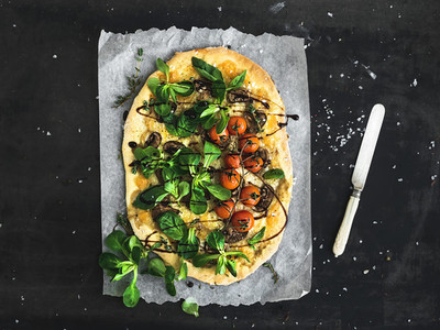 Rustic homemade pizza with fresh lambs lettuce mushrooms and cherry tomatoes over dark grunge background