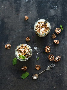 Walnut and salted caramel ice cream in glass jars with fresh mint over dark grunge backdrop  top view