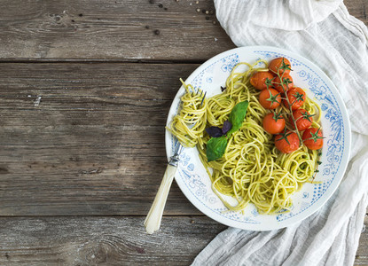 Pasta spaghetti with pesto sauce  basil  baked cherry tomatoes on rustic wooden tabke dark table  top view