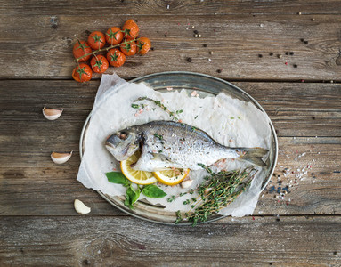 Roasted dorado or sea bream fish with vegetables  herbs and spices on silver tray over rustic wood backdrop  top view