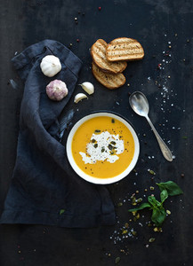 Pumpkin soup with cream  seeds  bread and fresh basil on grunge black background