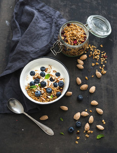 Healthy breakfast  Oat granola with fresh blueberries  almond  yogurt and mint in a rustic metal bowl