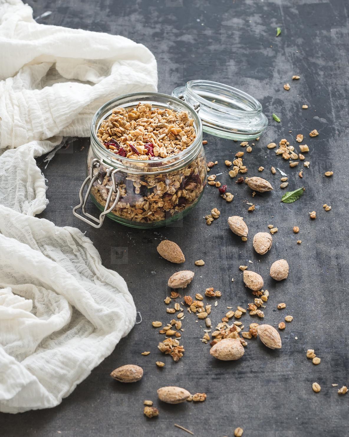 Oat granola in open glass jar on dark grunge backdrop
