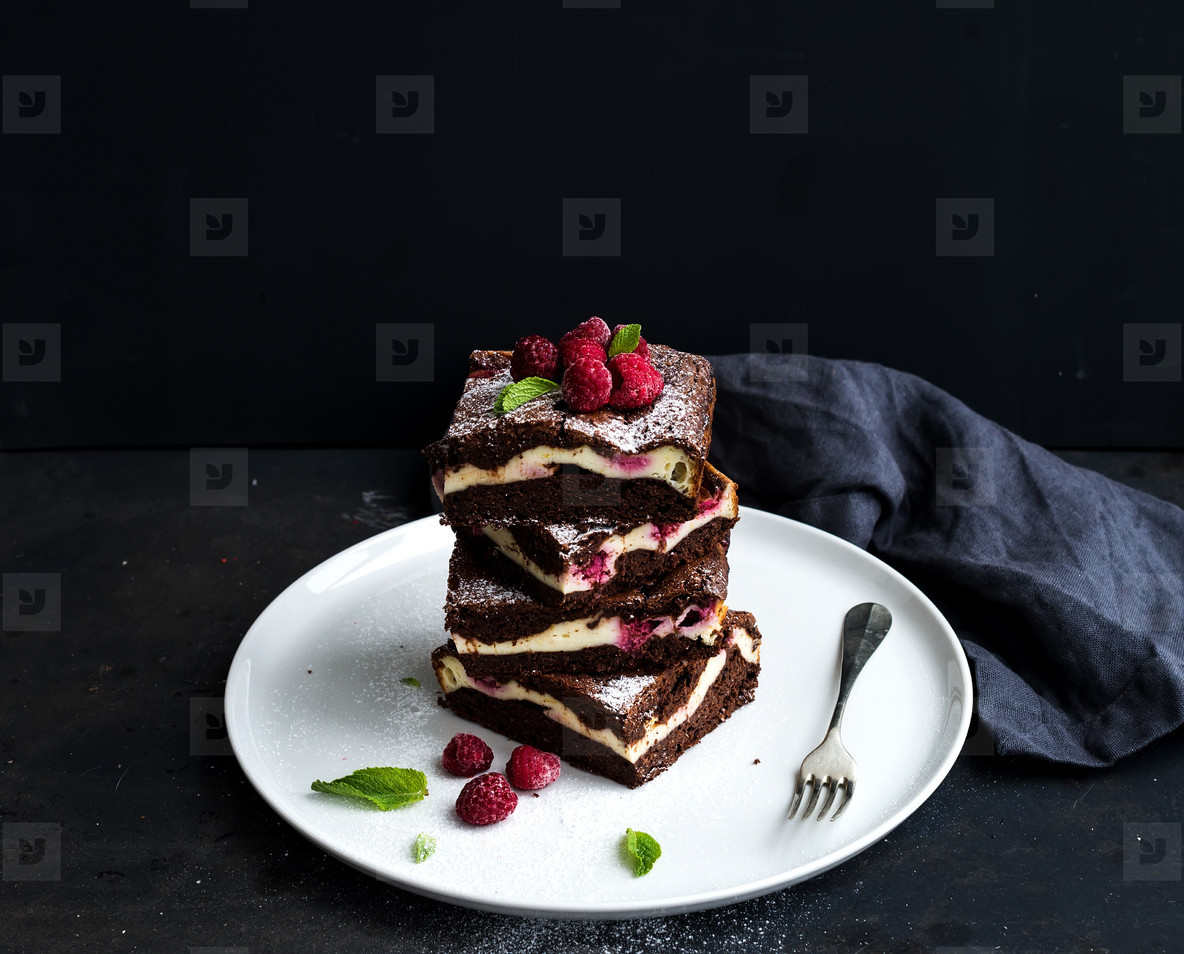 Brownie cheesecake tower with raspberries on white plate  black backdrop  copy space