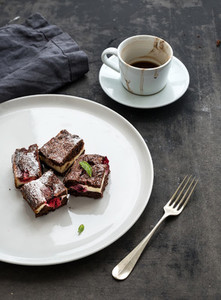 Cheesecake brownie squares with raspberries and coffee on white ceramic plate over dark grunge table surface