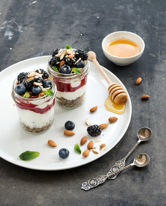Yogurt oat granola with berries  honey and nuts in glass jars  dark grunge background