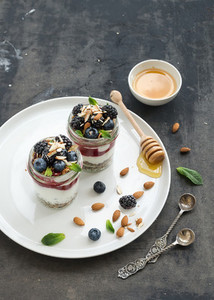 Yogurt oat granola with berries  honey and nuts in glass jars  dark grunge background