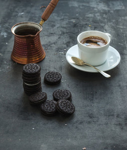 Chocolate cookies with cup and pot of coffee  dark grunge backdrop