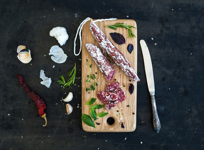 Meat gourmet snack  Salami  garlic and herbs on rustic wooden board over dark grunge backdrop