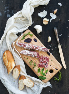 Meat gourmet snack Salami garlic baguette and herbs on rustic wooden board over dark grunge backdrop