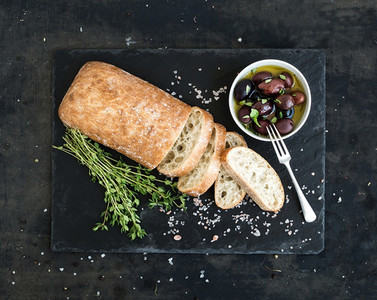Italian ciabatta bread cut in slices on wooden chopping board with herbs  garlic and olives over dark grunge backdrop  copy space