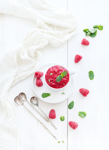 Raspberry sorbet ice cream with mint leaves  and spoons on white background