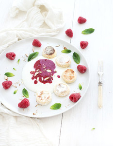 Rustic breakfast set  Russian cottage cheese cakes on ceramic plate with berry jam  almonds  fresh raspberries and mint over white wooden backdrop  top view